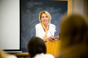 Instructor Sharon Adams lecturing at podium.