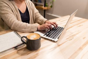 View of someone typing on a laptop with a cup of coffee.